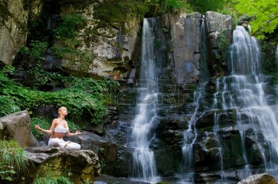beautiful-young-woman-meditating-in-lotus-position-while-doing-yoga-in-a-wonderful-forest-near-water