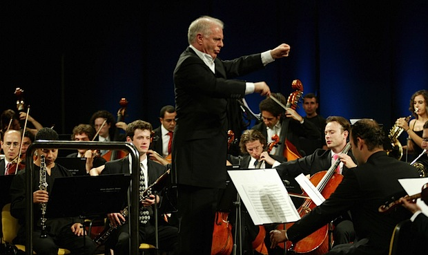 RAMALLAH, -: Argentine-Israeli Daniel Barenboim conducts the Jewish and Arab musicians of the West-Eastern Divan Orchestra, jointly founded by late US-Palestinian intellectual Edward Said and Barenboim, during a solidarity concert in the West Bank city of Ramallah, 21 August 2005. Members of the orchestra, based in Spain and comprising around 100 musicians from Egypt, Jordan, Lebanon Egypt and Israel, are travelling on diplomatic passports issued by Madrid to limit holdups at Israeli checkpoints. The Ramallah concert is the climax of a tour that has taken the orchestra to cities including Buenos Aires and London. AFP PHOTO/ABBAS MOMANI (Photo credit should read ABBAS MOMANI/AFP/Getty Images)