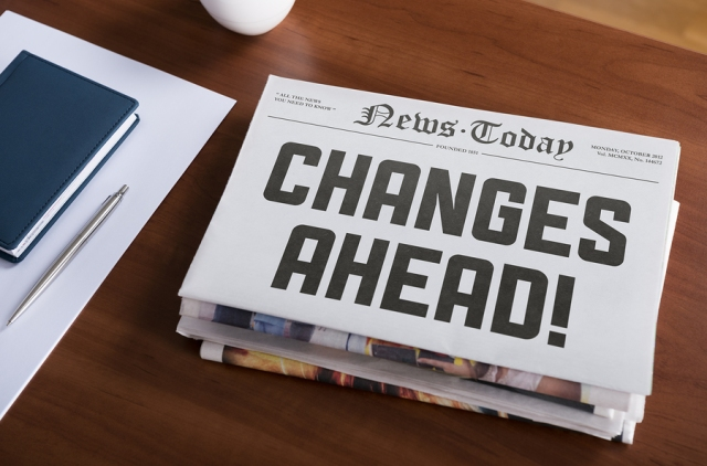 "Newspaper with hot topic ""Changes Ahead"" lying on office desk."